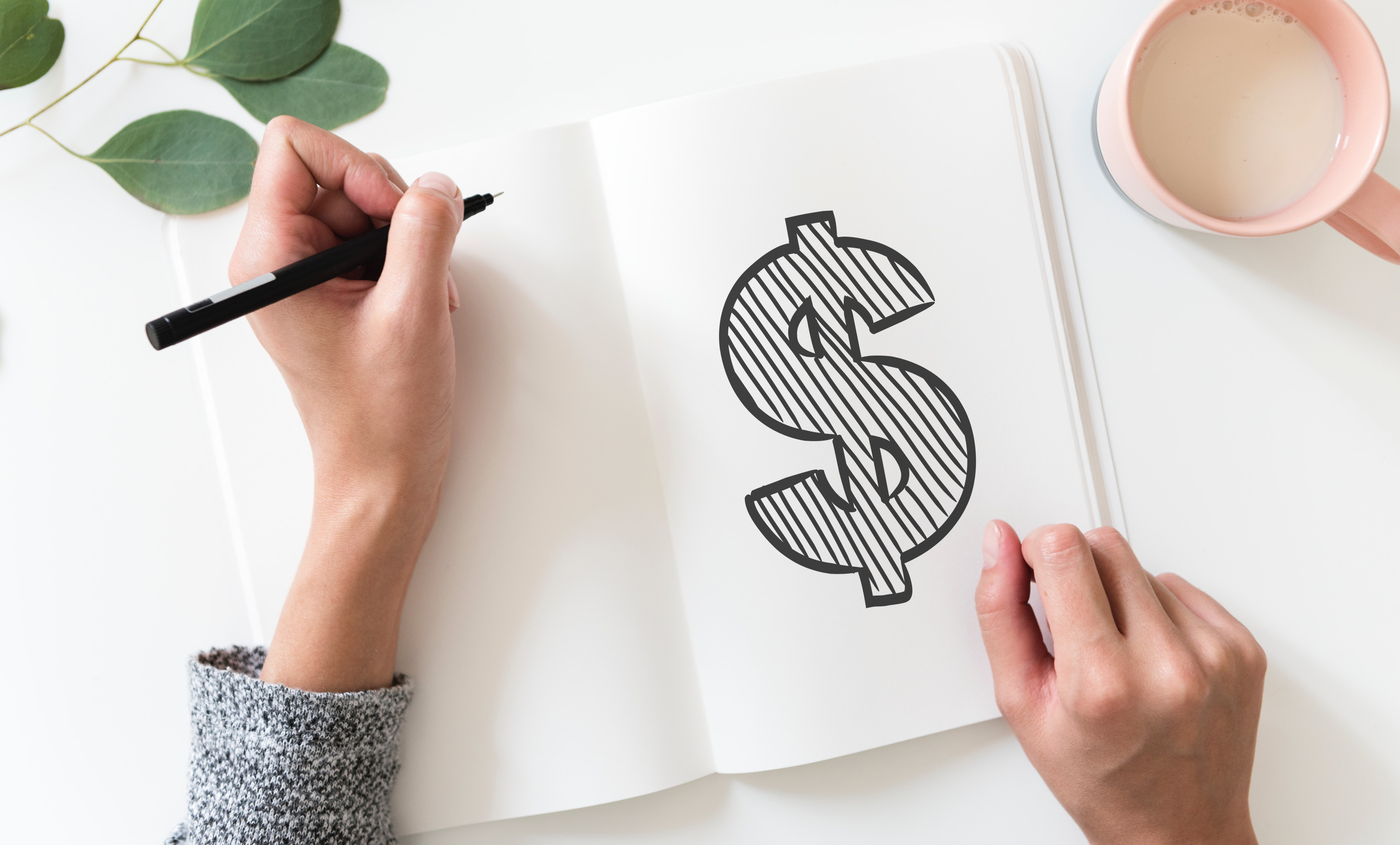Woman's hands drawing a dollar sign on a piece of paper